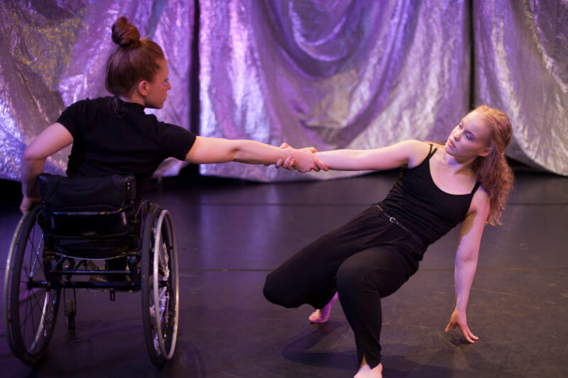 Två dansare varav en i rullstol. De håller varandra i handen, den ena med ryggen mot och den andra närmre golvet.