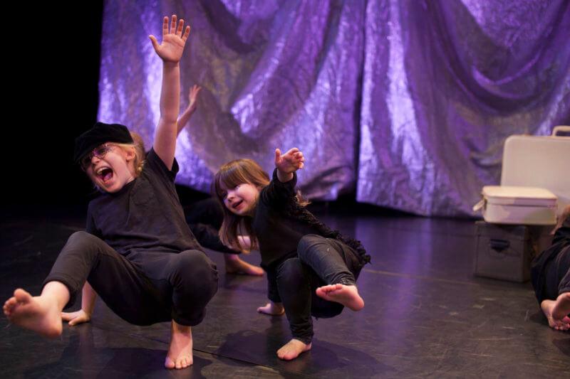 Två barn dansar nära golvet med bara en hand och en fot i golvet.