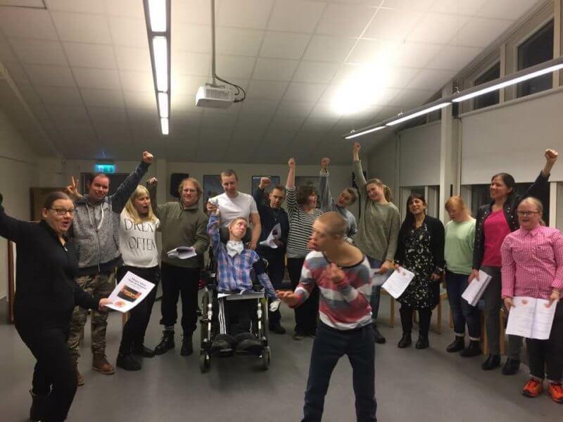 En grupp som sjunger tillsammans och sträcker ut armarna.